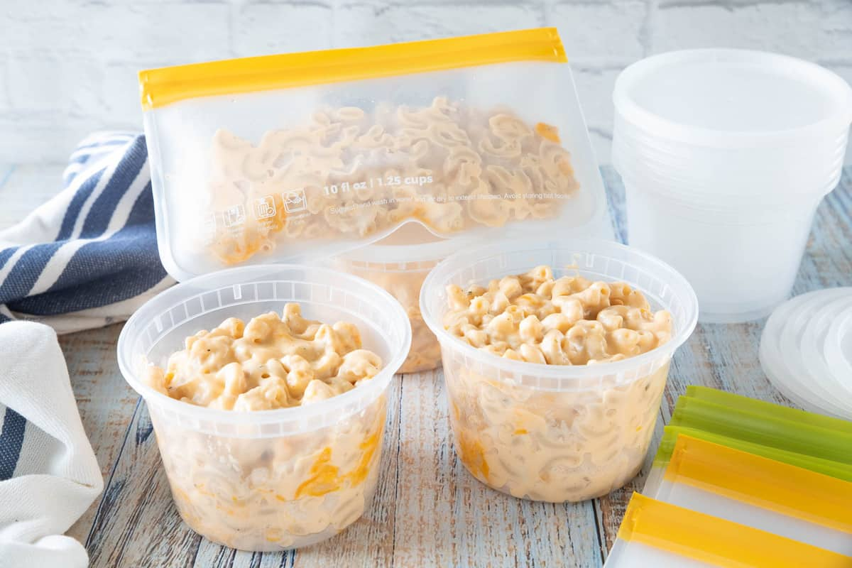 Plastic containers filled with Mac and cheese ready to be frozen.