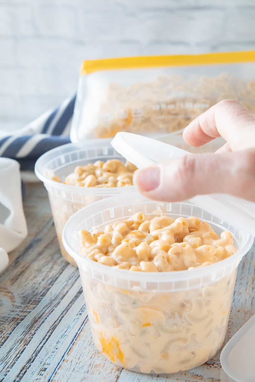 A hand placing a lid on top of a plastic container of Mac & cheese.