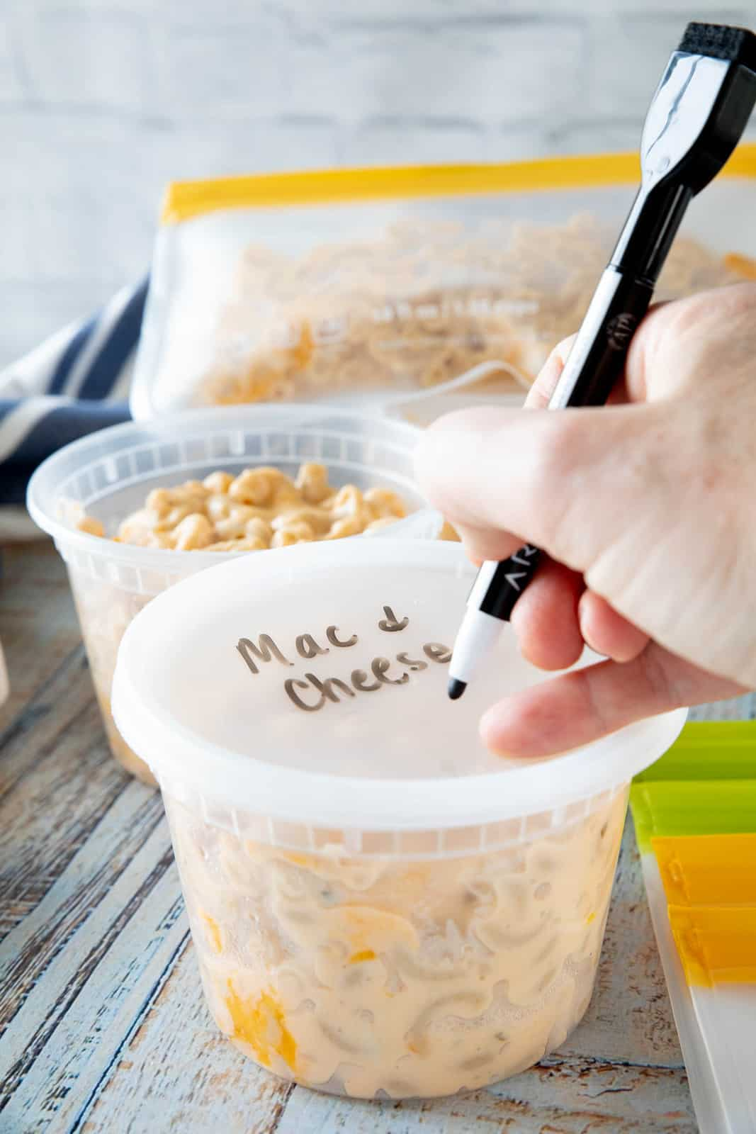 A hand writing Mac & cheese on top of a plastic lid that is on top of a plastic container filled with pasta.