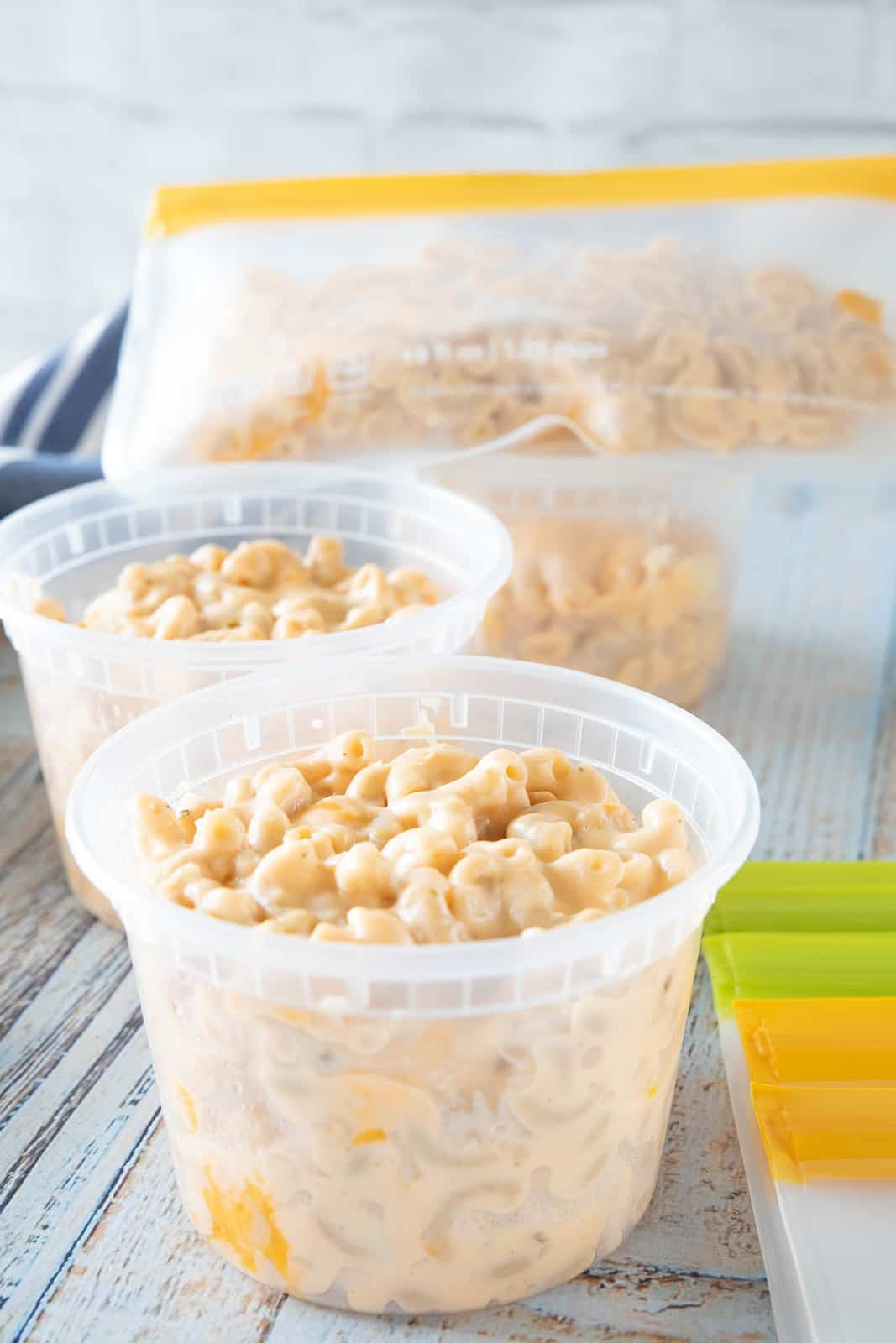 Mac & cheese being shown in plastic containers that are on top of a countertop.
