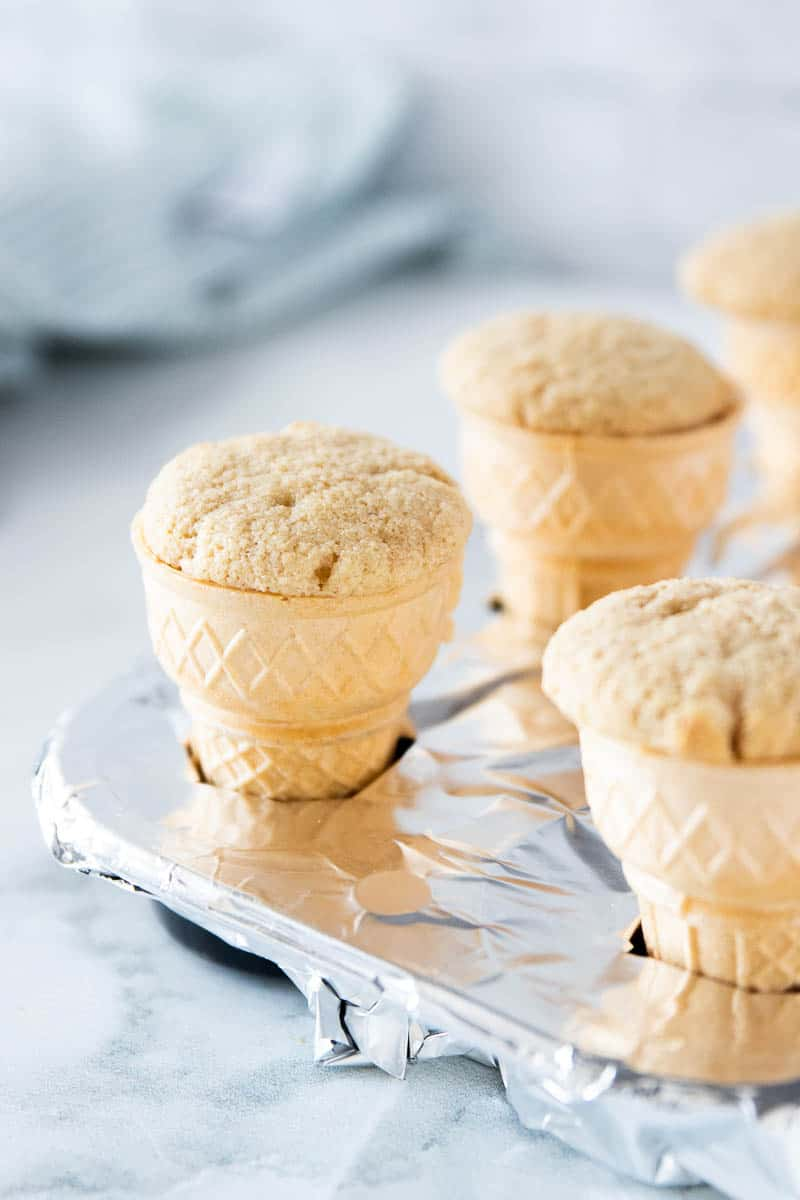 A tinfoil lined muffin tin being shown with an ice cream cone cupcake in each tin.