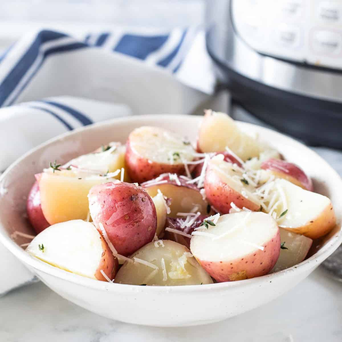 Red potatoes sprinkled with parmesan cheese in a bowl.