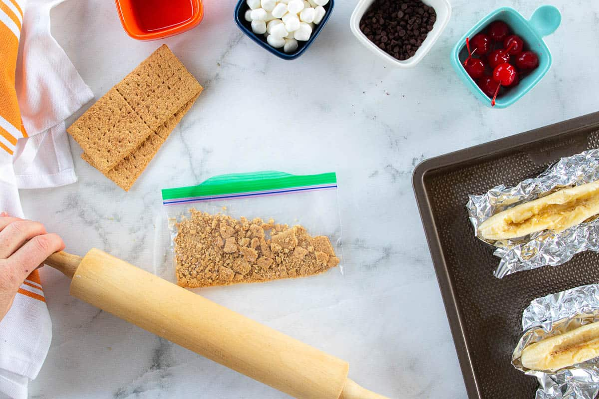 Graham cracker crumbs being crushed with a rolling pin with various ingredients surrounding the bag of crumbs.