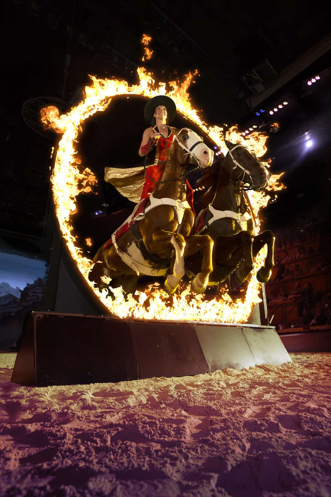 women on two horses jumping through a ring of fire