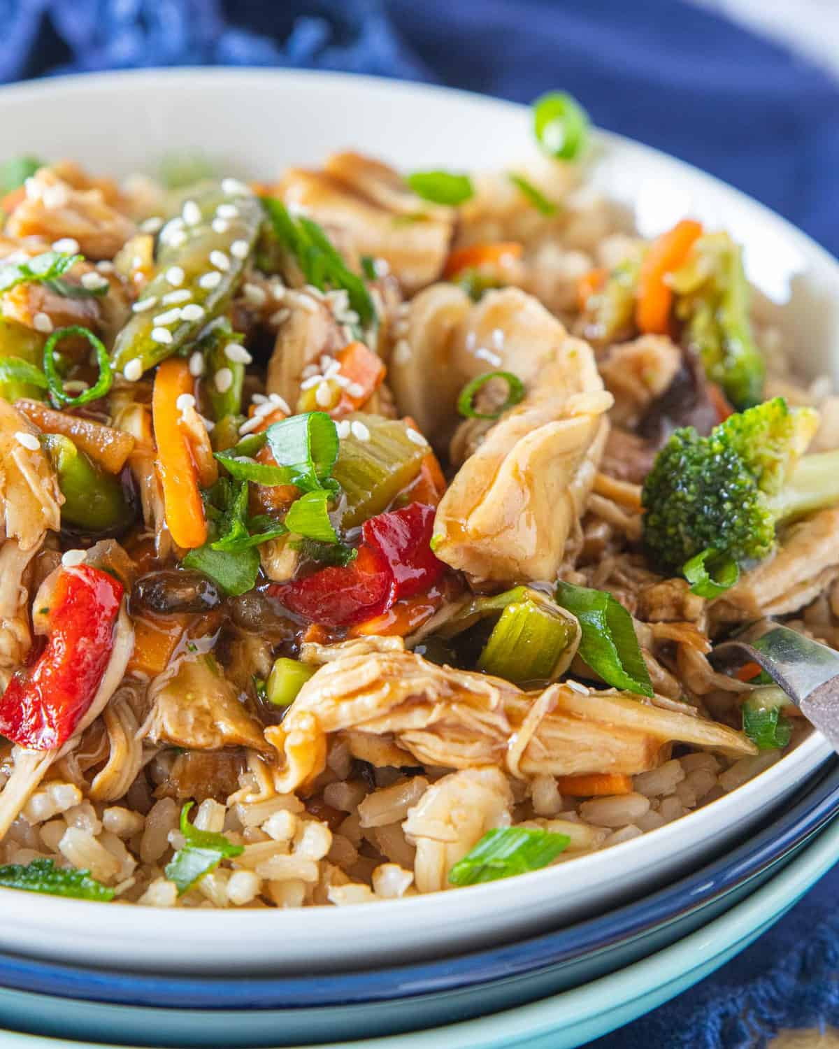instant pot chicken stir fry on top of a bed of rice in a bowl.