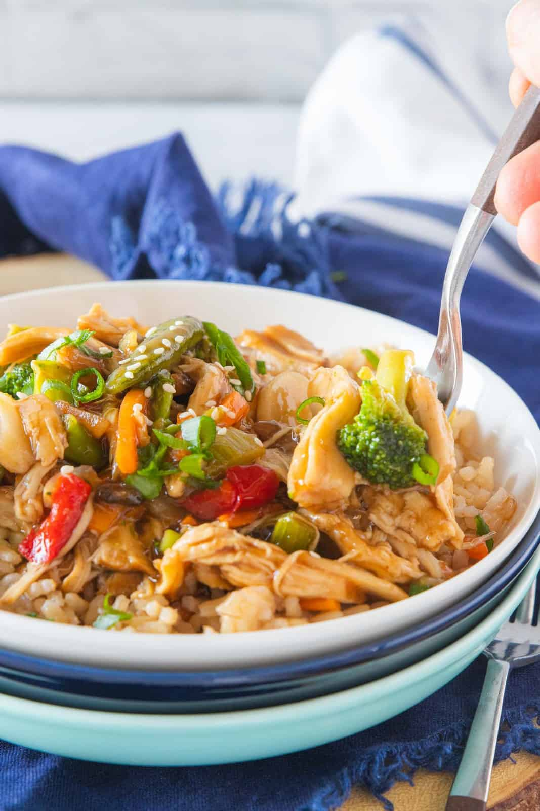 A fork scooping a serving of chicken stir fry.