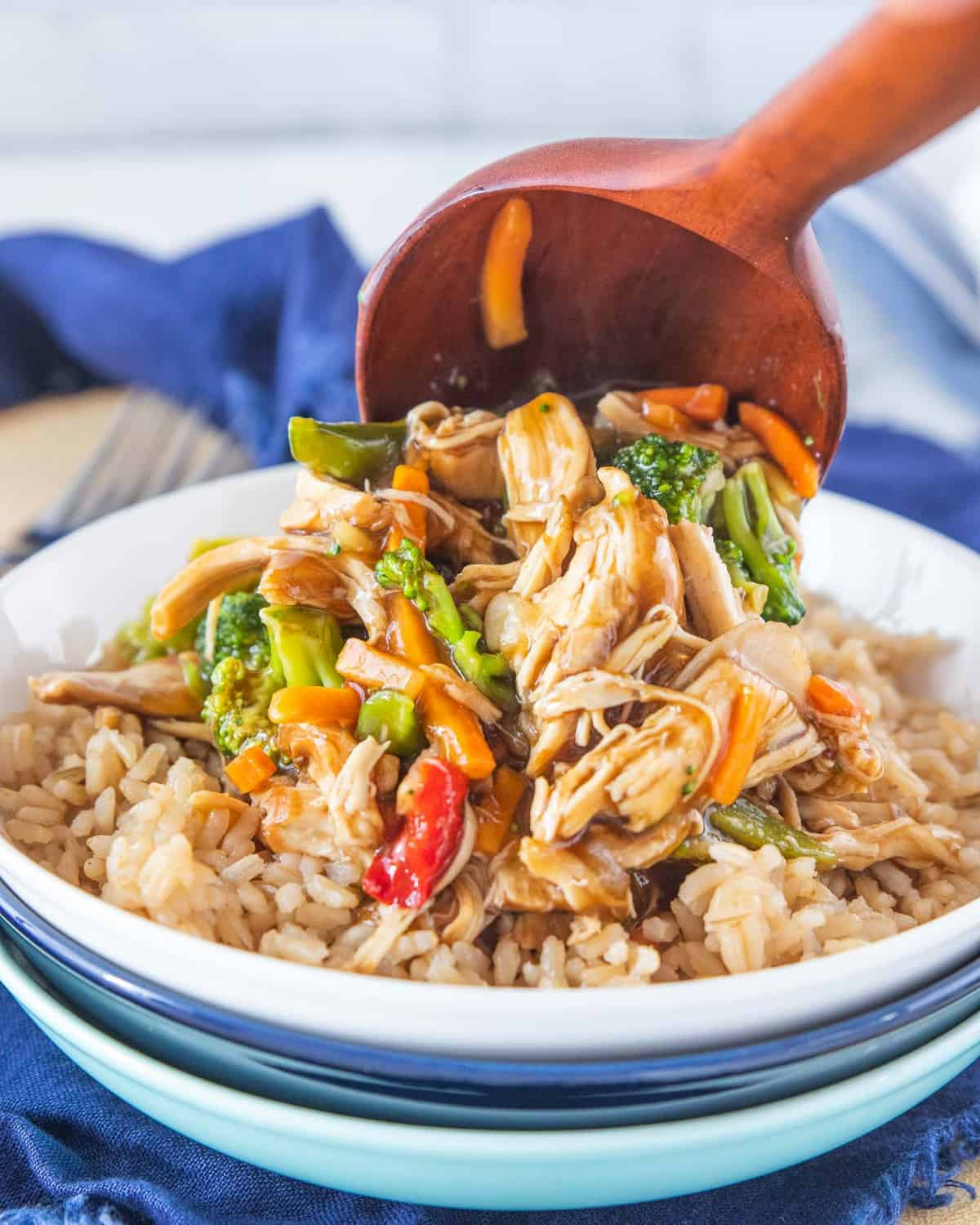 Chicken stir fry scooped over a bed of rice in a bowl.