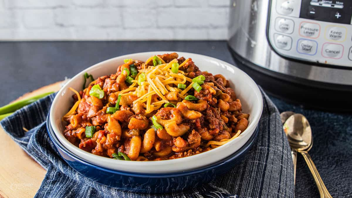 instant pot chili mac in a bowl topped with cheese