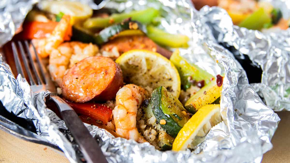 shrimp, veggies and rice in a foil pack with a fork.