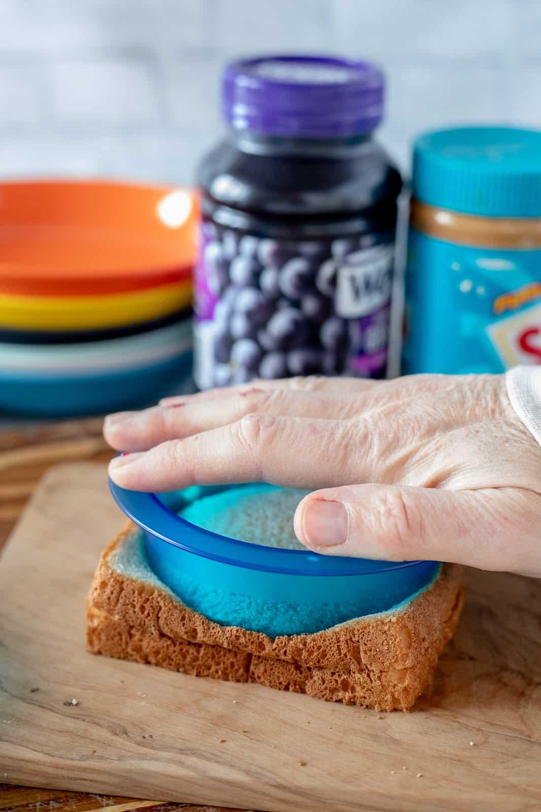 hand pressing an uncrustable cutter onto bread