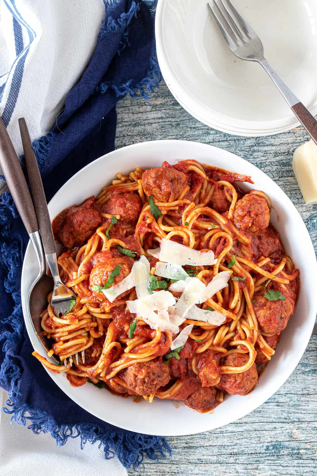 spaghetti and meatballs in a bowl with shredded parmesan on top