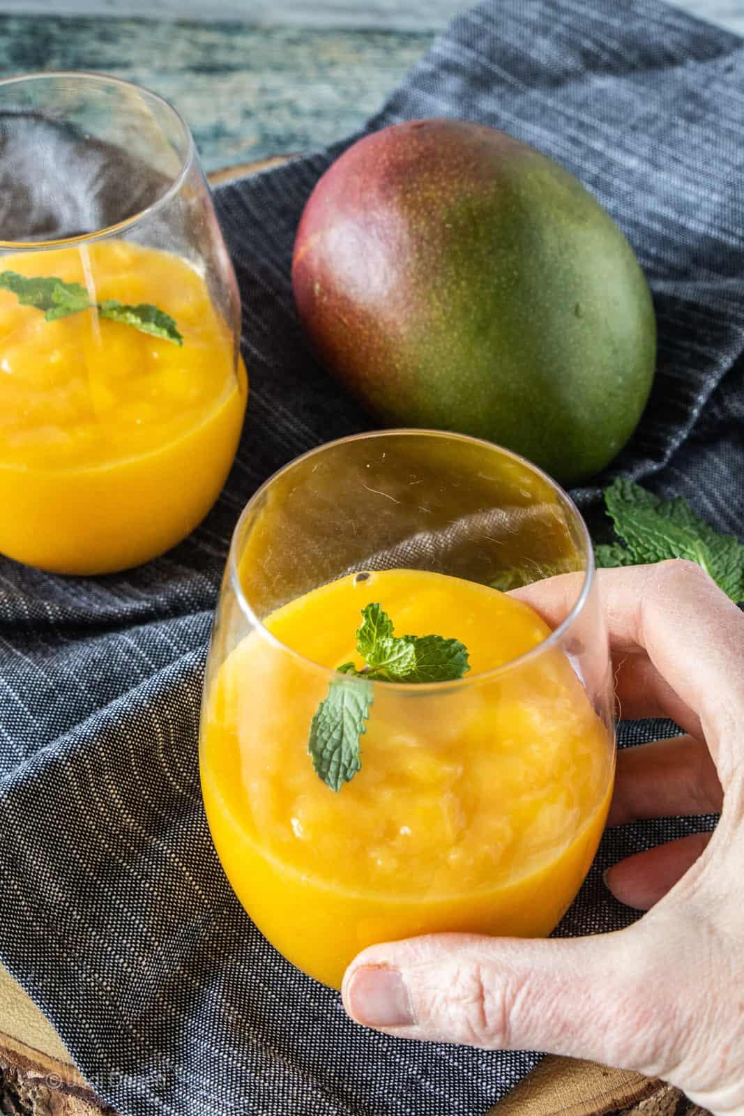 hand holding a mango drink