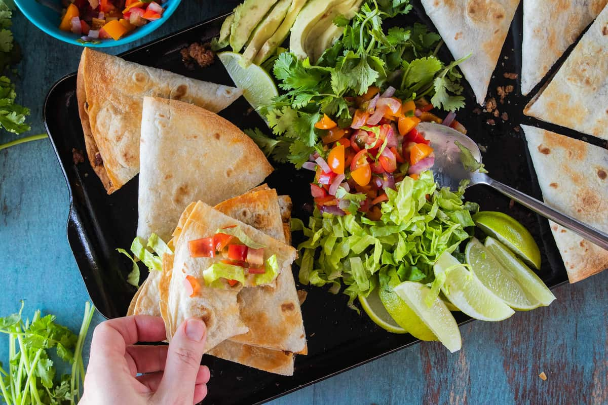 quesadilla on serving tray with toppings