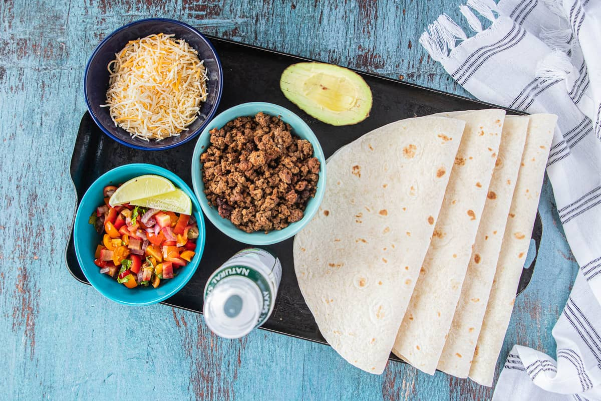 ingredients for taco quesadillas on a tray