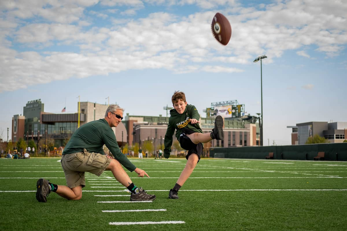 father and son playing football at Lambeau Field