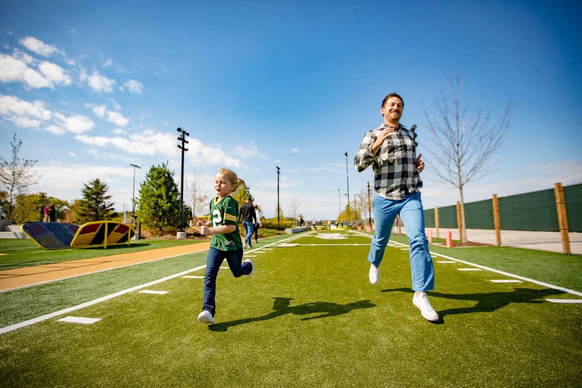 Family running on a football field