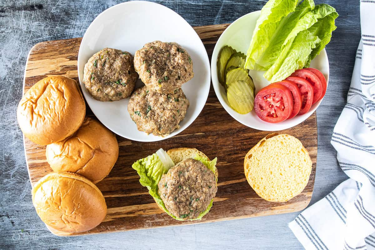 turkey burgers surrounded by buns and toppings