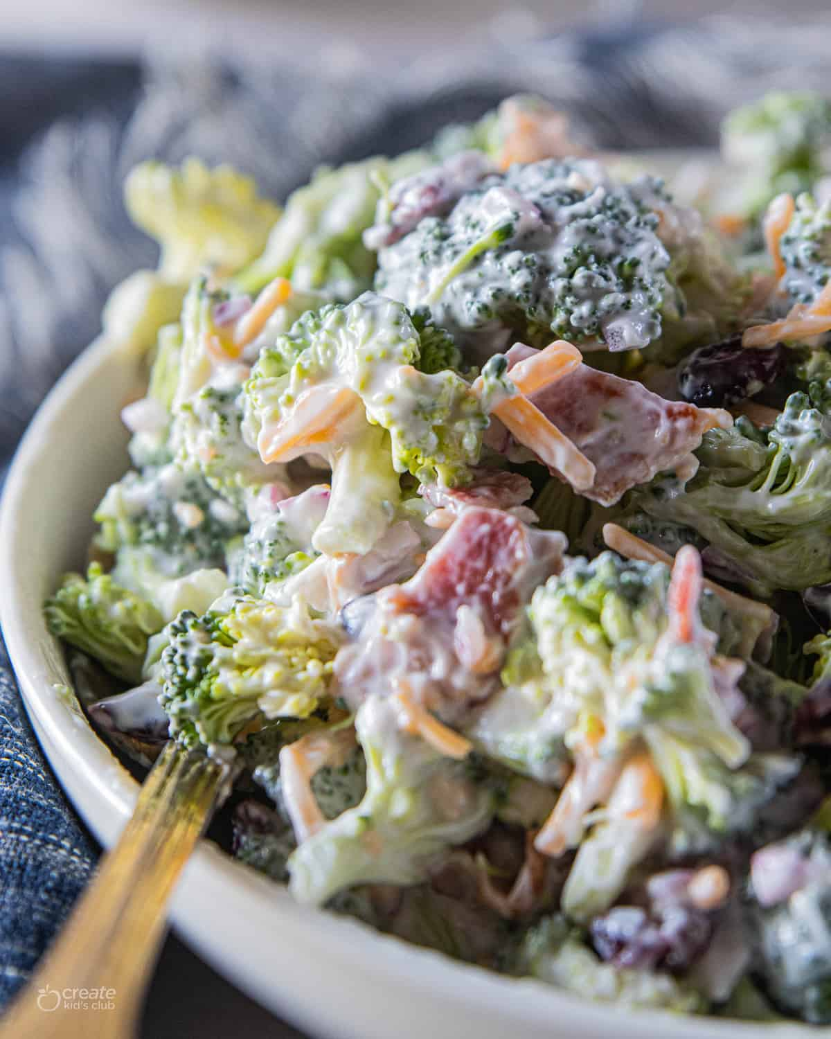 Broccoli salad in serving bowl with a spoon