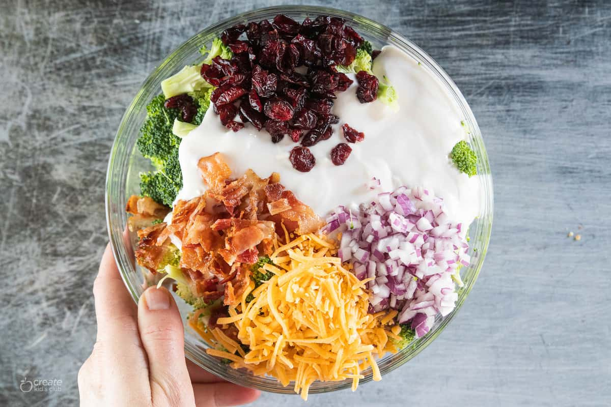 salad ingredients with dressing in a mixing bowl