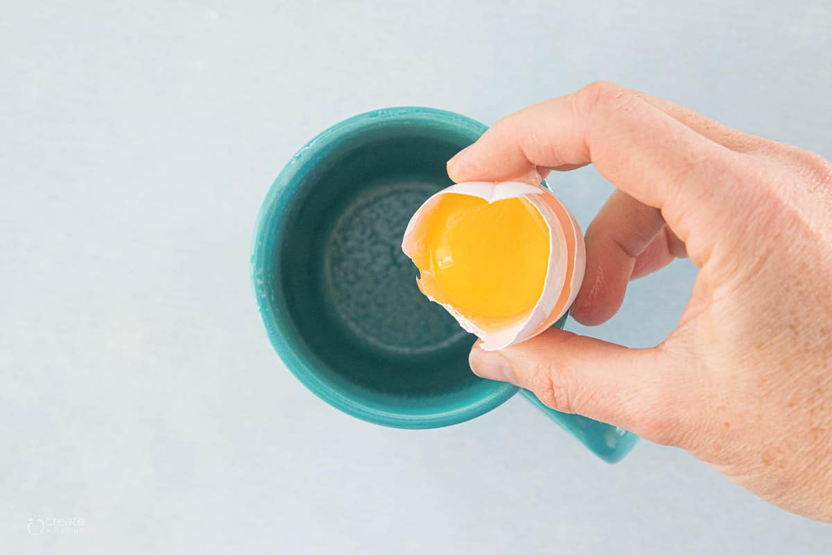 egg yolk being added to a mug