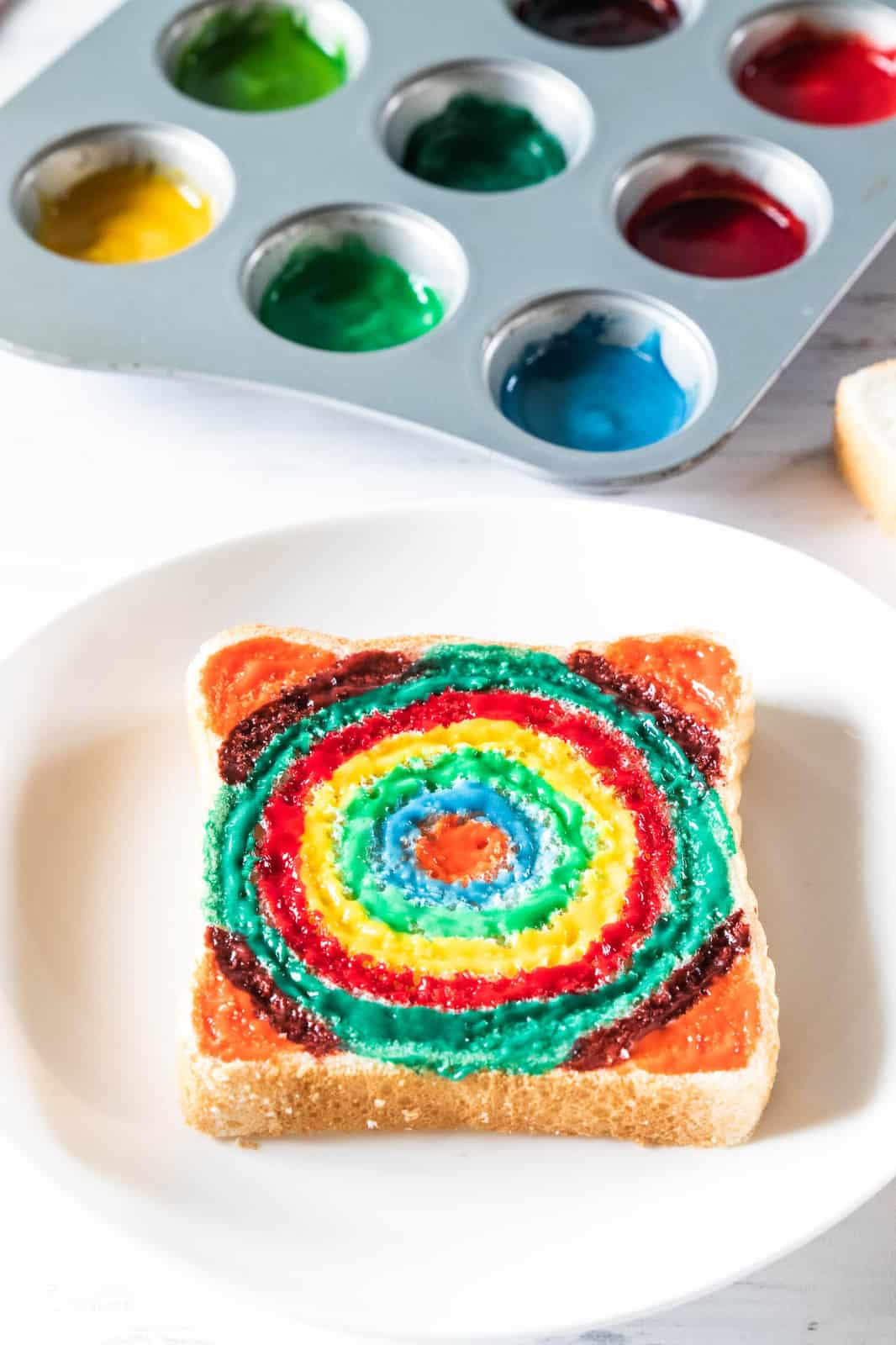 finger paint colors in a muffin tin and a painted piece of bread