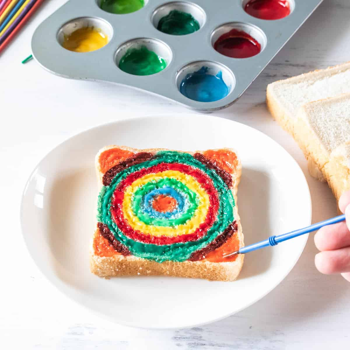 slice of bread being painted with edible paint