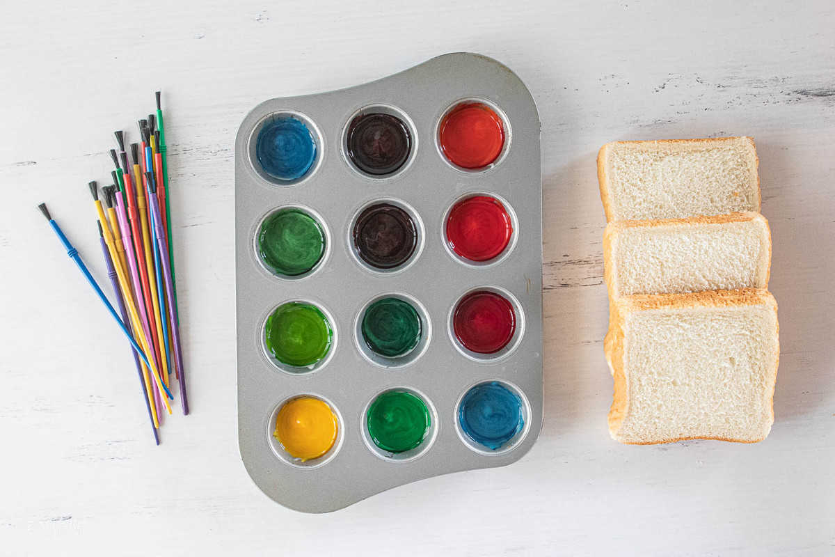 paint colors in a muffin tin with slices of bread and paint brushes next to the tin