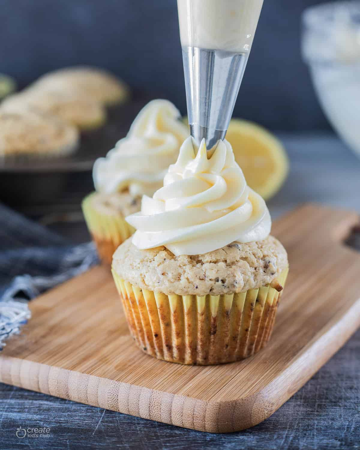lemon cream cheese icing piped on top of a cupcake