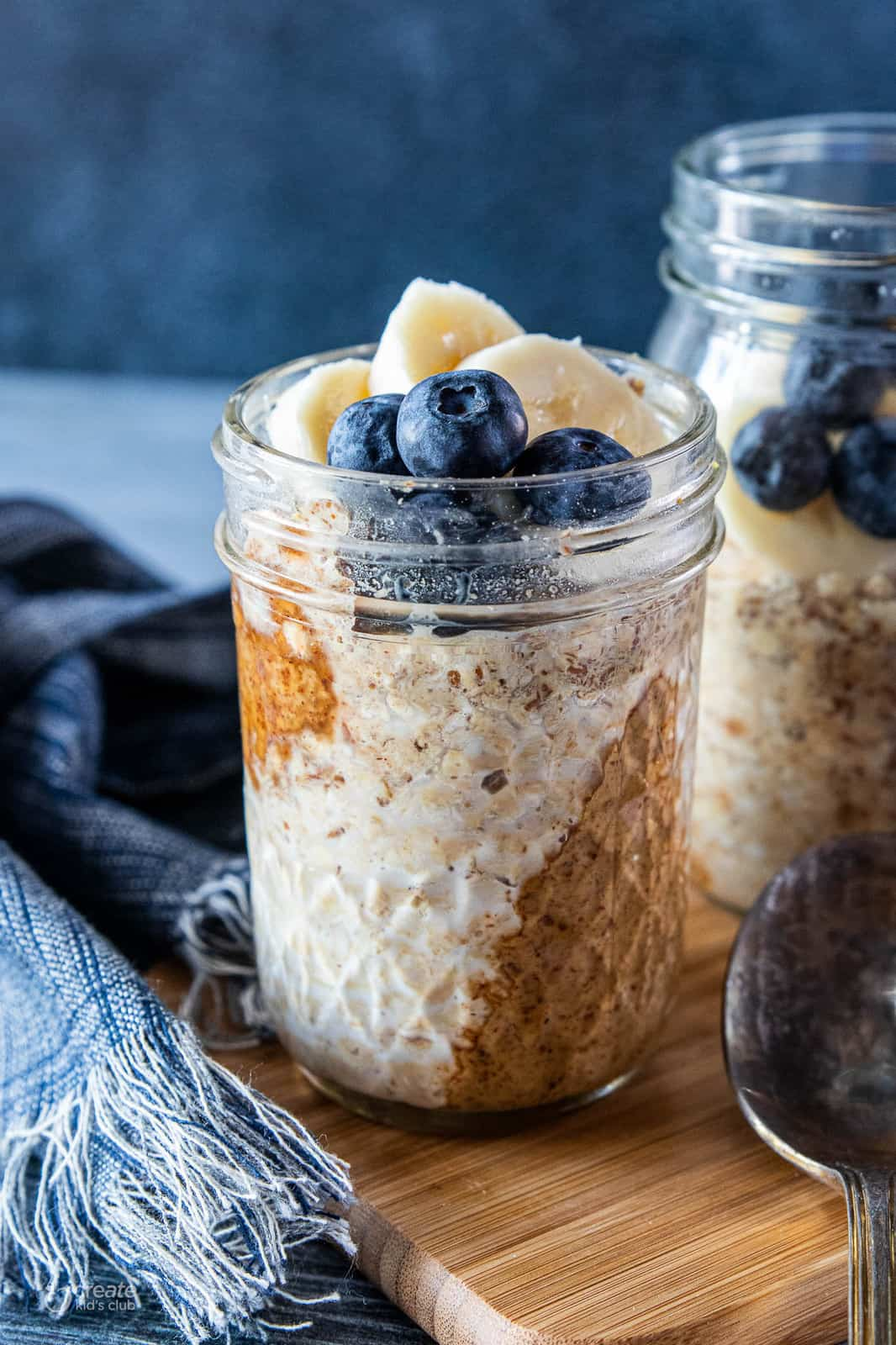 Peanut butter overnight oats in mason jars topped with fresh blueberries and banana slices