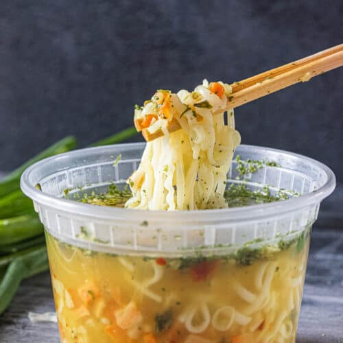 chopsticks removing ramen noodles from container