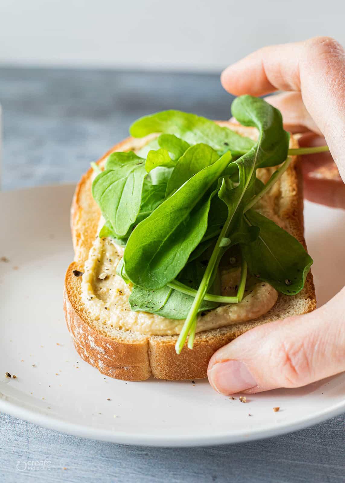 hummus and arugula on toast