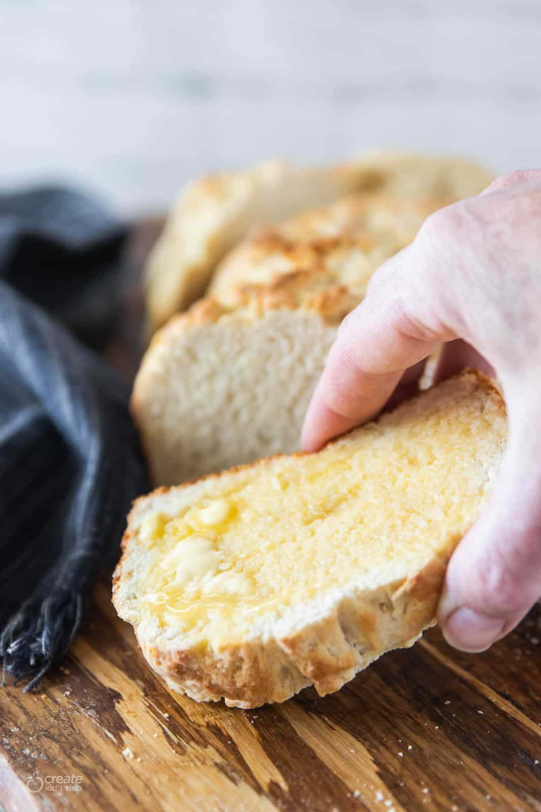 hand picking up slice of homemade bread with butter