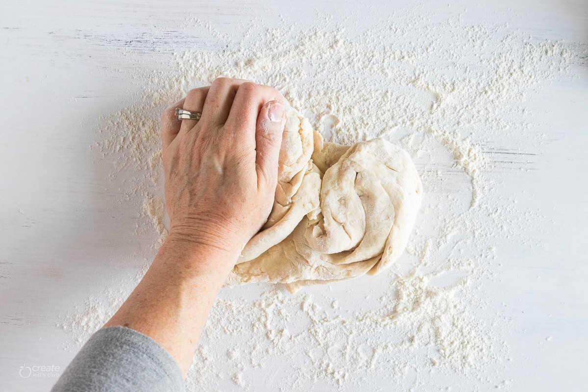 hand kneading bread dough on floured surface