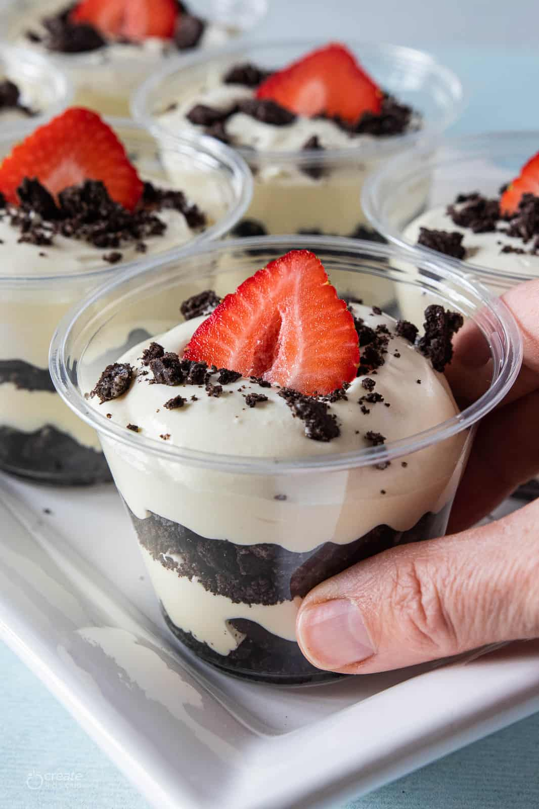 layers of crumbled oreos and pudding in cups topped with a strawberry slice
