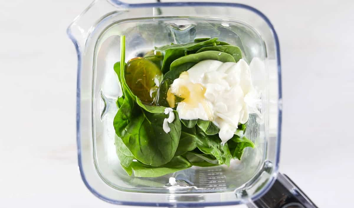 A top down view into a blender showing spinach, yogurt, and honey.
