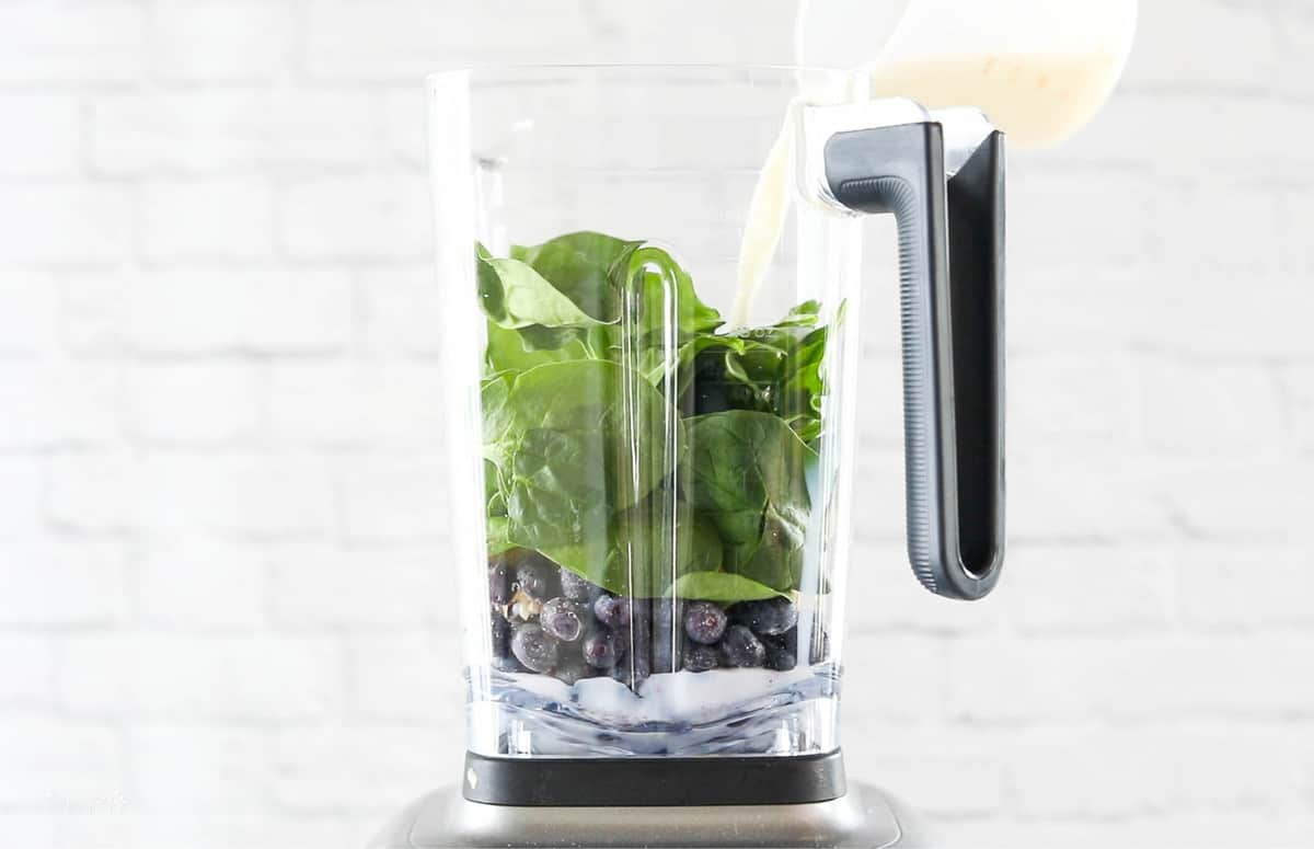 A front view of a blender with blueberries, spinach, and milk being added.