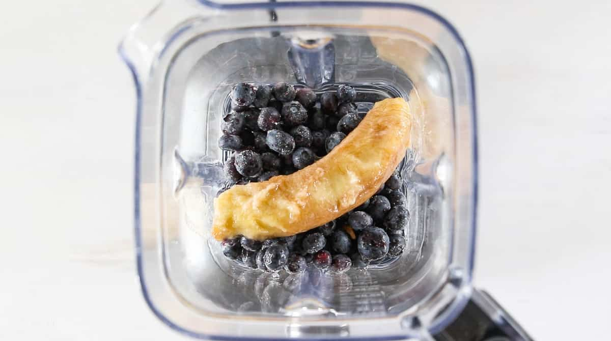 A top down view into a blender with frozen blueberries and a frozen banana.
