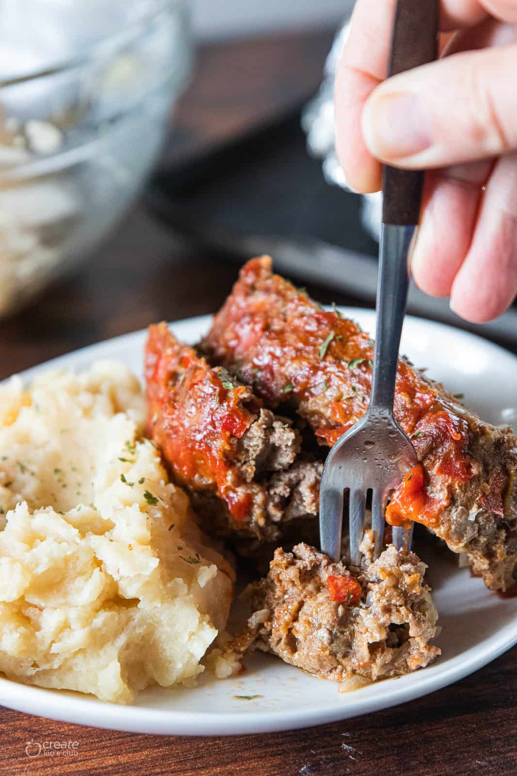 meatloaf on plate with mashed potatoes with a fork
