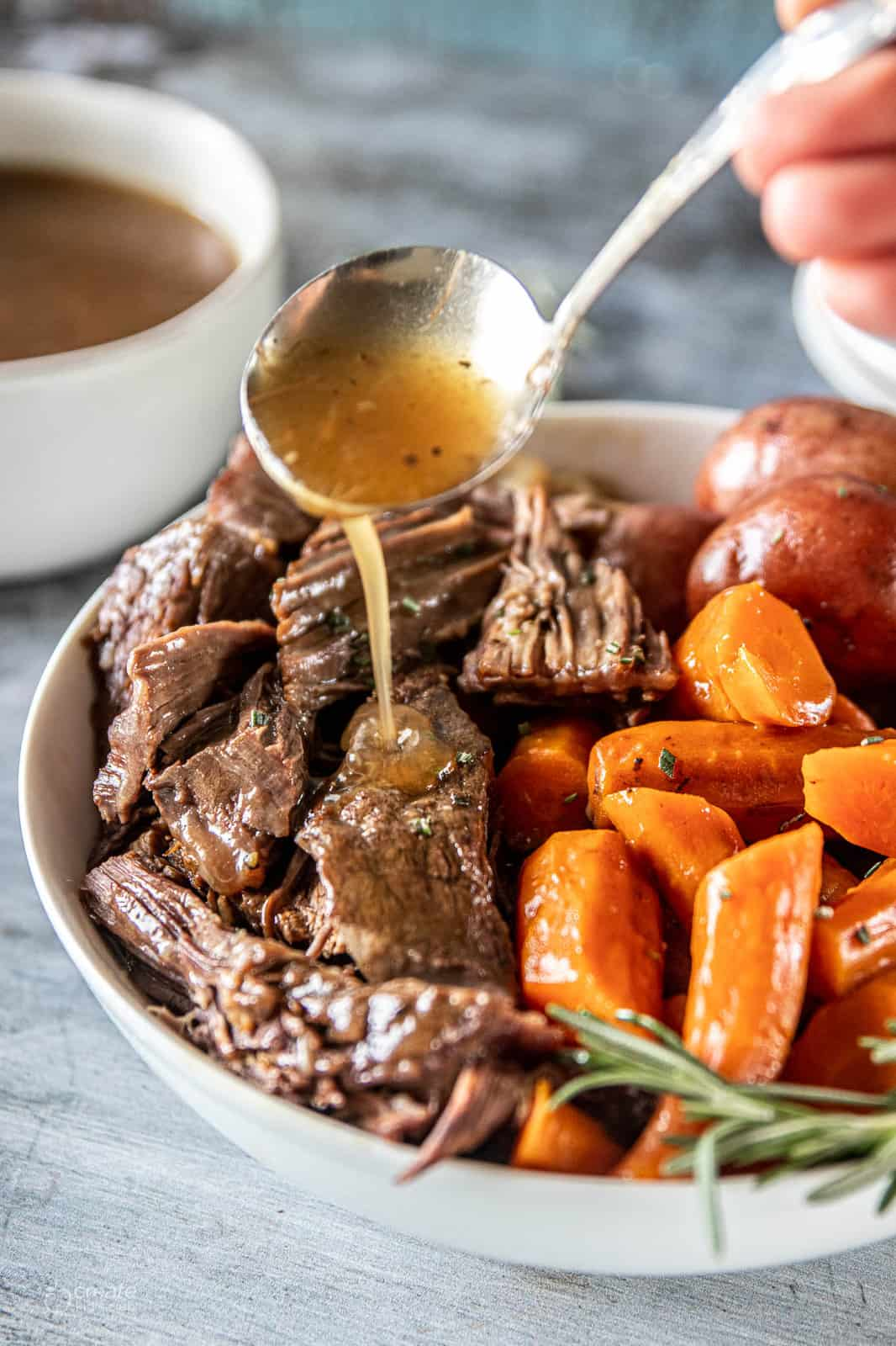 Instant pot roast beef showing gravy being drizzled over it next to carrots and potatoes.