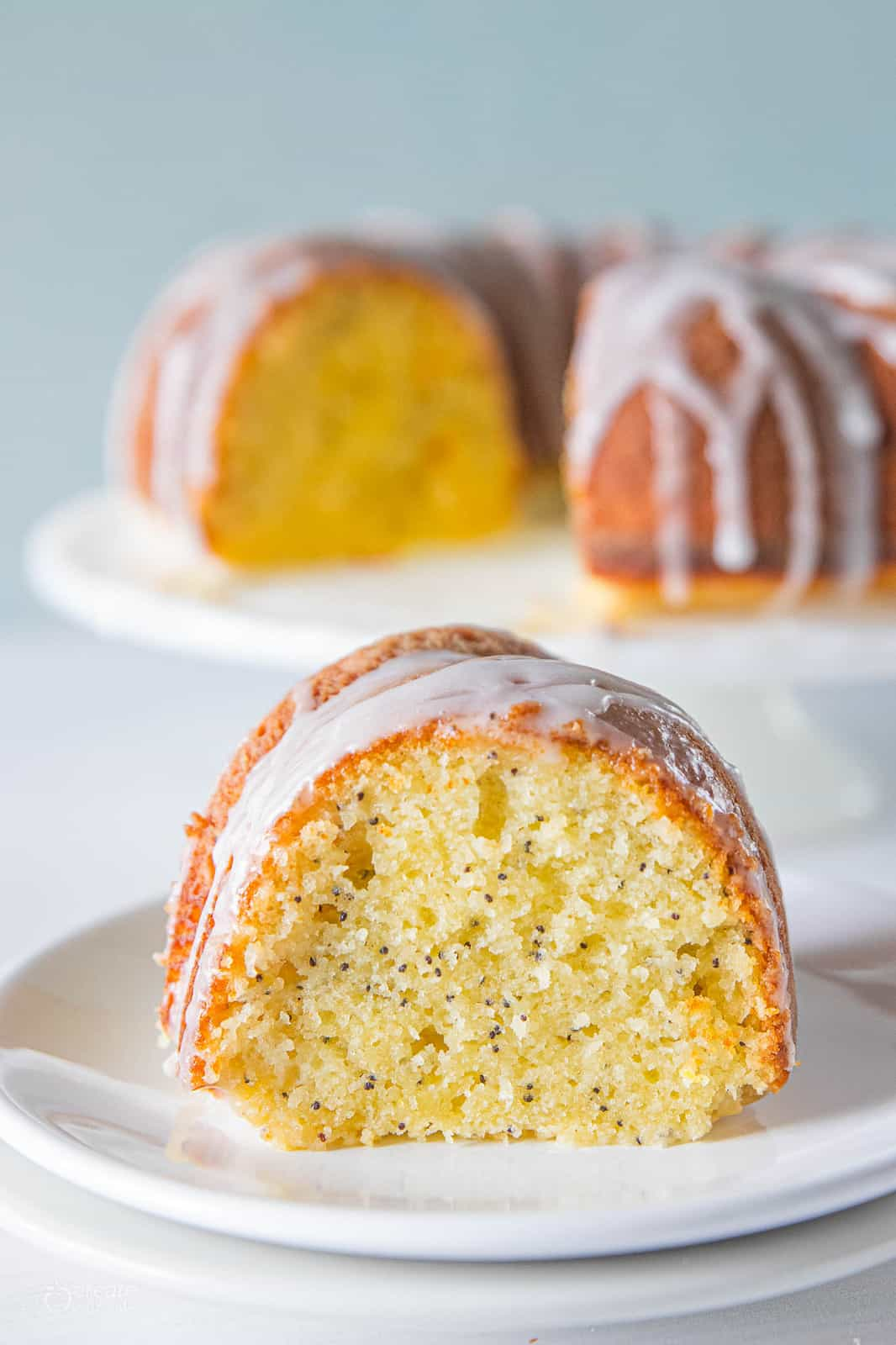 slice of lemon poppyseed cake drizzled with icing on plate