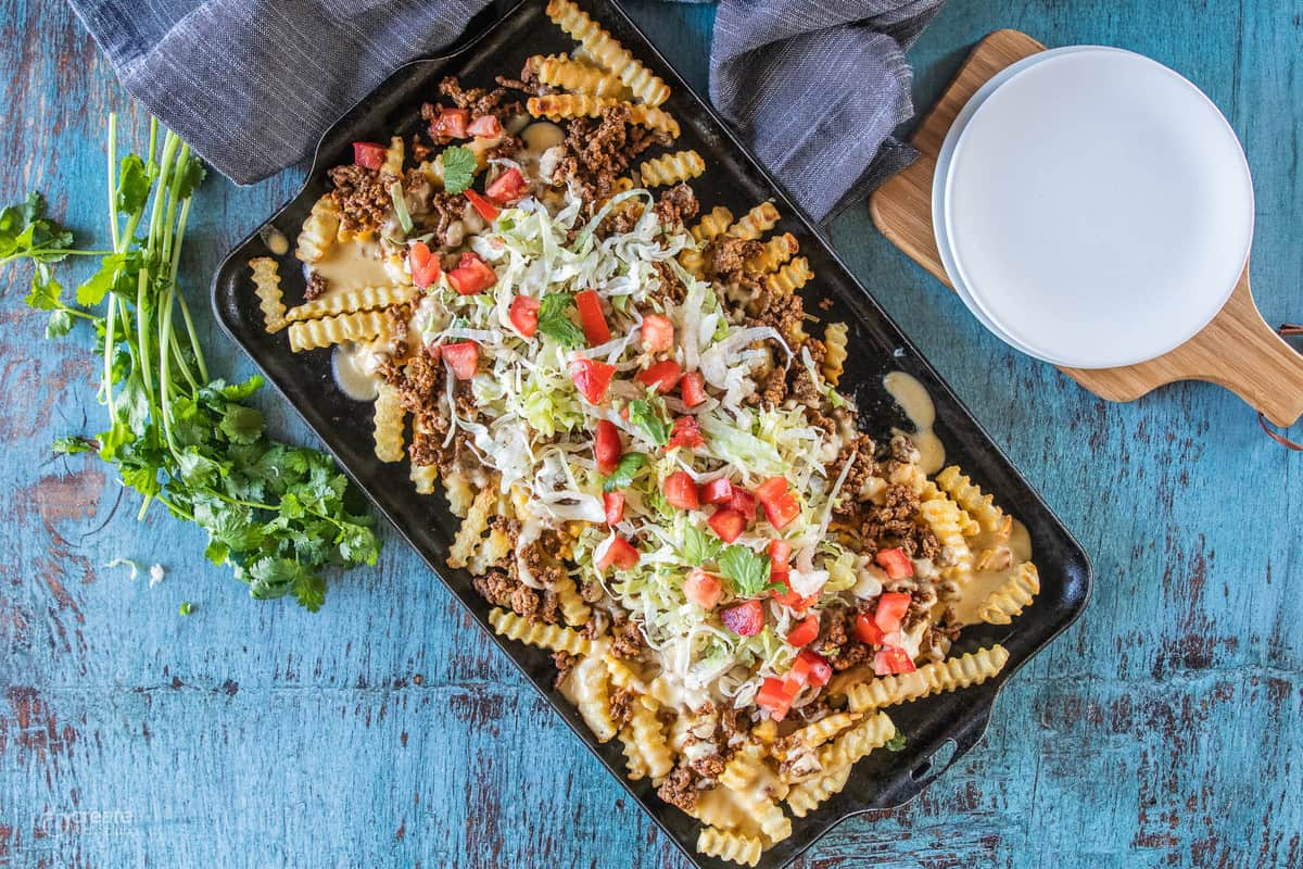 cheesy fries topped with lettuce and tomato on a baking dish
