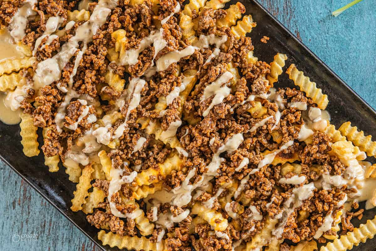 fries with meat and cheese sauce on a baking dish.