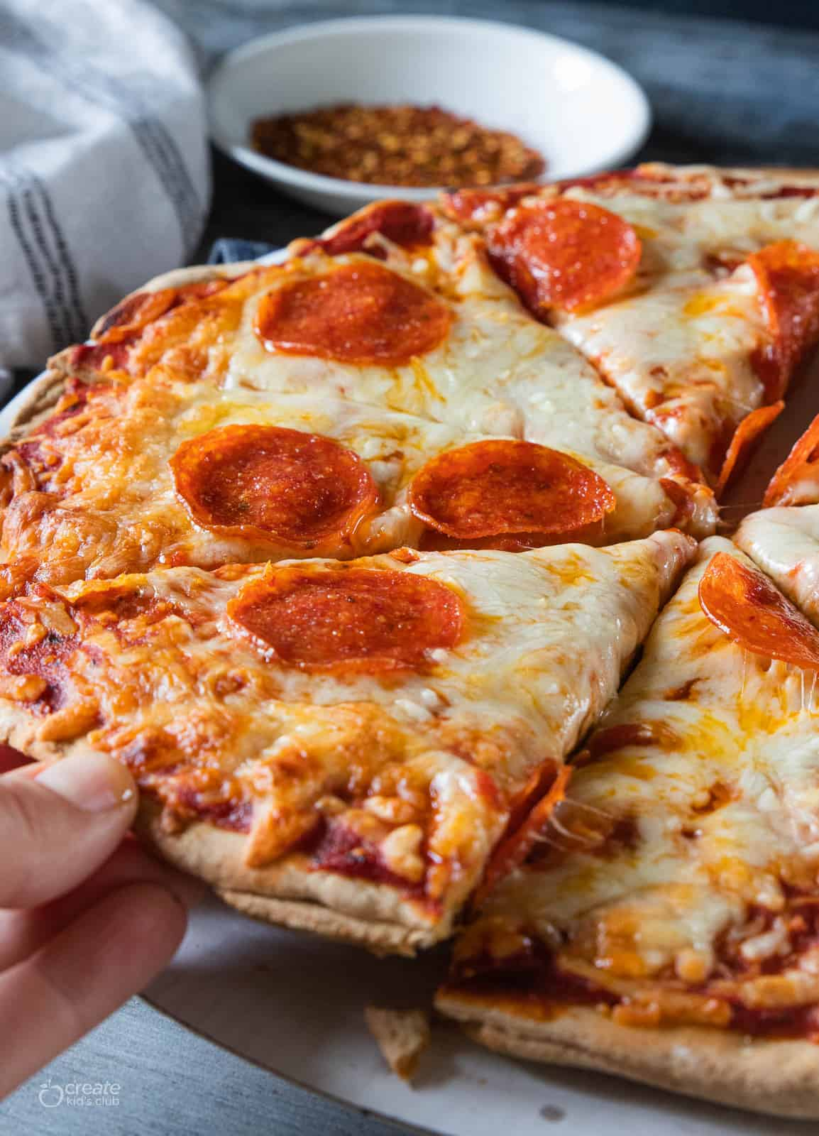 A hand is taking a slice of hot homemade pizza.