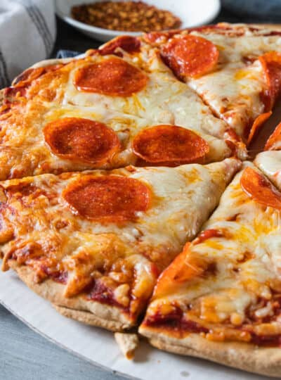 Baked homemade pizza with wheat crust shown sliced.