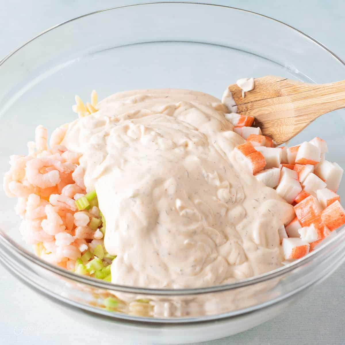 seafood ad creamy style dressing in bowl with wooden spoon