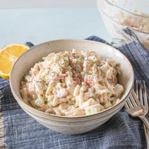 Seafood salad with orzo pasta in a bowl.