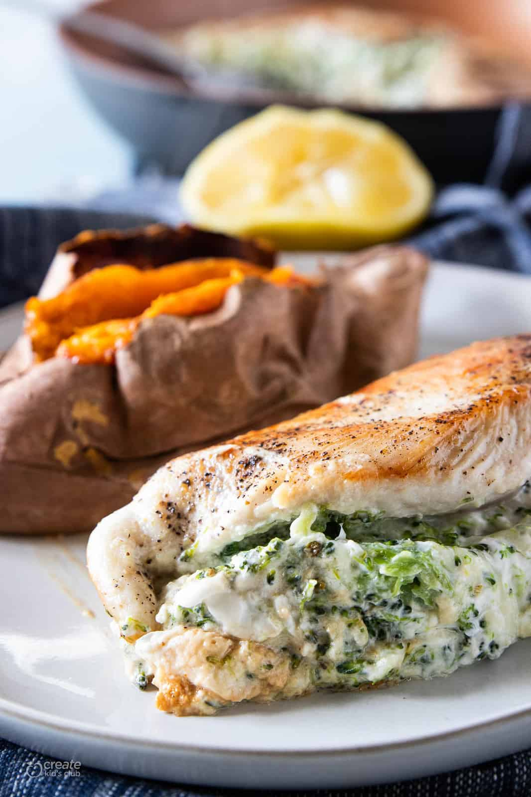 veggie and cheese stuffed chicken on plate with a sweet potato