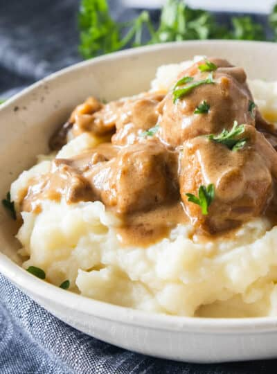 swedish meatballs on top of mashed potatoes in a bowl