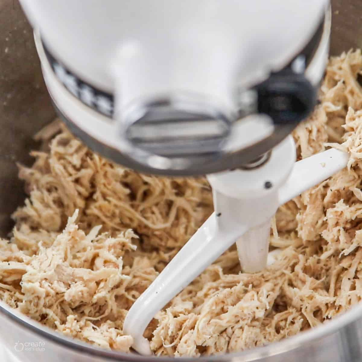 A close up of shredded chicken in a kitchenaid mixer being shredded.