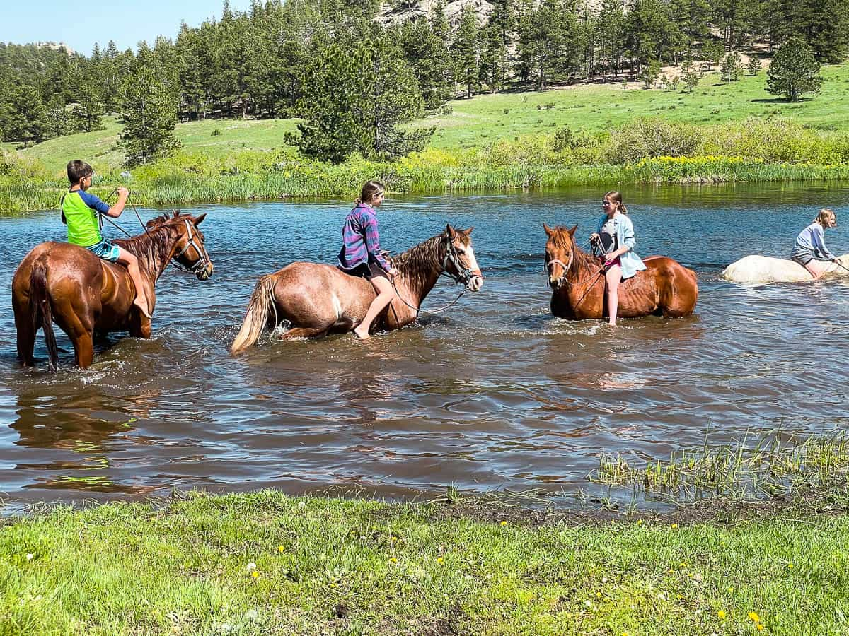 kids riding horses in water